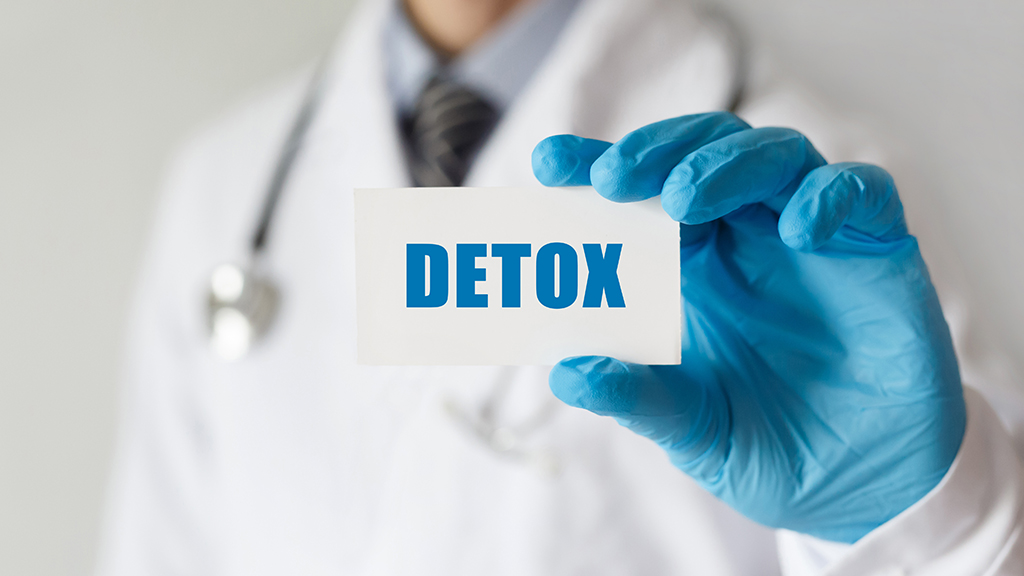 Doctor holding a card with text DETOX, medical concept